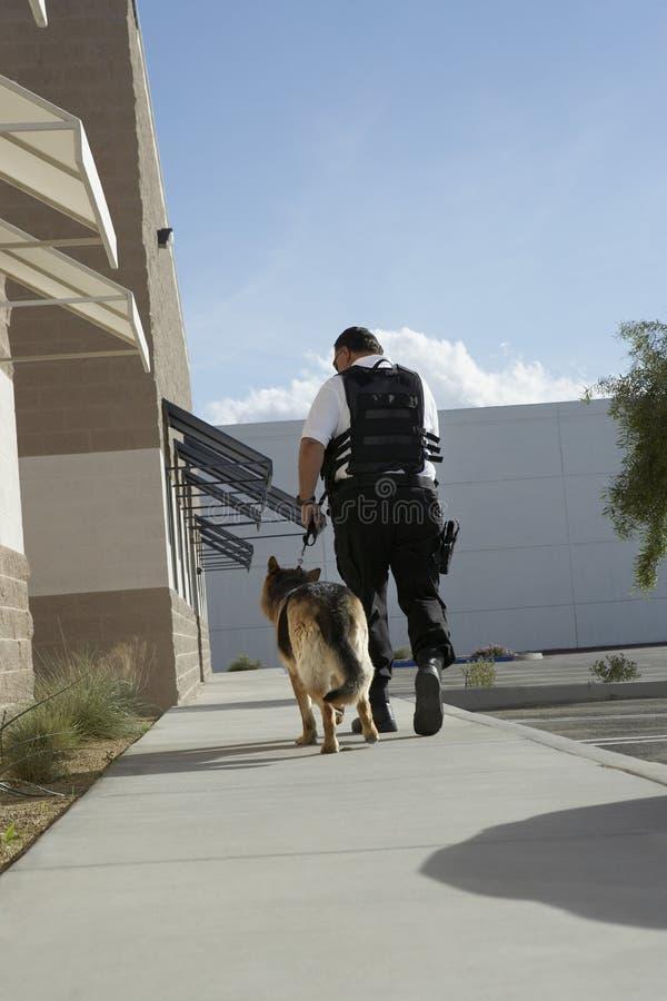 Sicherheitsbeamte-With Dog On-Patrouille stockfotografie