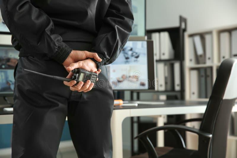 Sicherheitsbeamte mit dem Übermittler des portablen Radios, der moderne Überwachungskameras im Überwachungsraum überwacht stockfotos