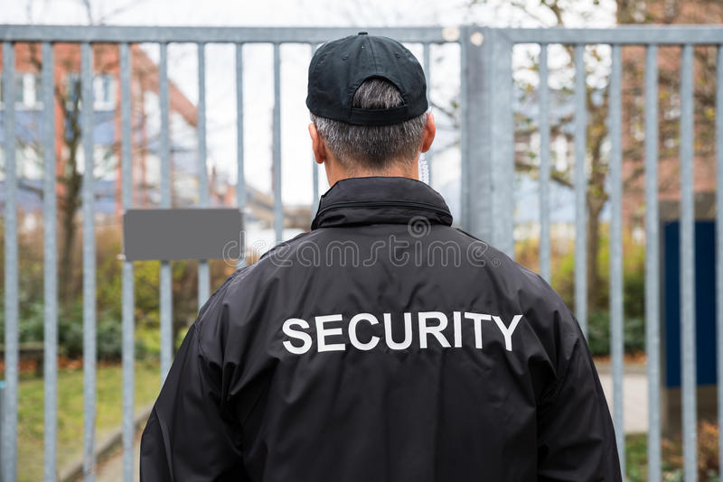 Sicherheitsbeamte Standing In Front Of Gate stockbild
