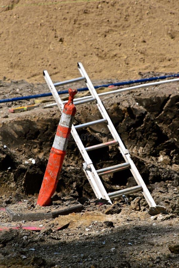 Sicherheitskegel erkennt Gefahr, wohin eine Leiter aus einem Graben heraus erreicht lizenzfreies stockbild