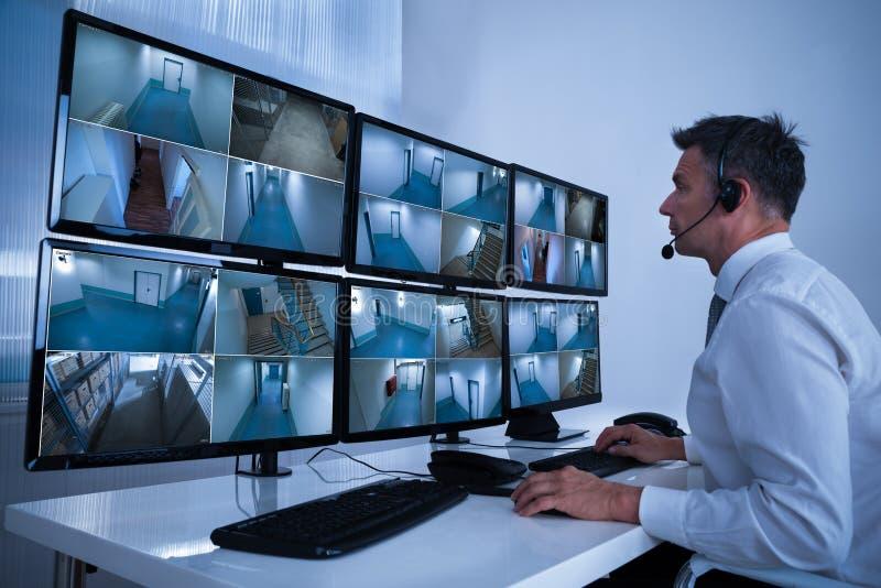 Sicherheitssystem-Betreiber, der Bänder von Überwachungskameras auf Schreibtisch betrachtet lizenzfreie stockfotografie