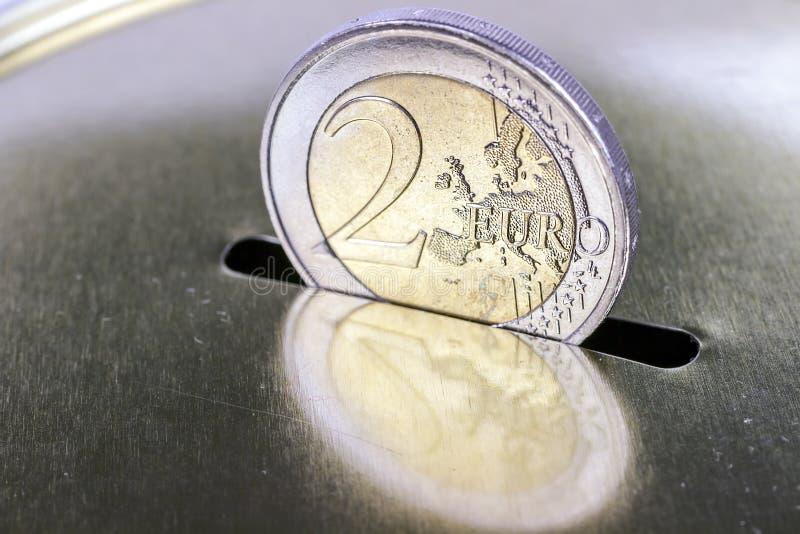 Sicherung von zwei Euros in einer piggy Querneigung stockfotos