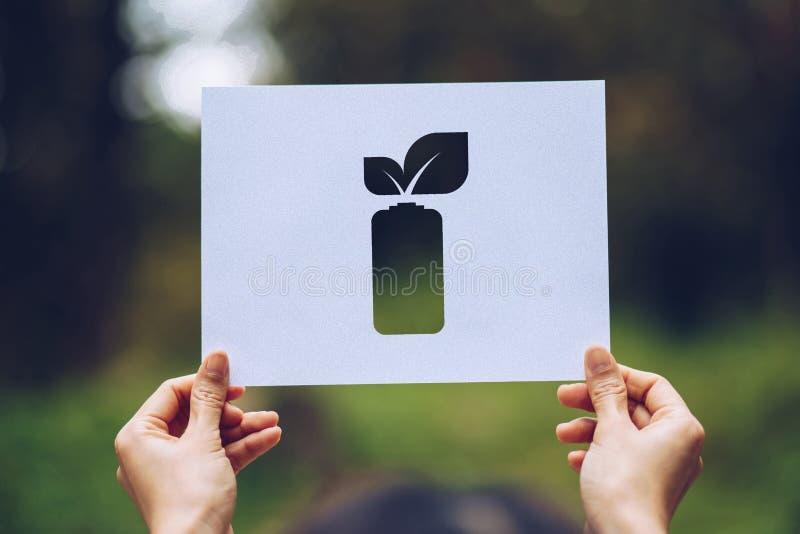 Sicherungsweltökologie-Konzept-Klimaerhaltung mit den Händen, die herausgeschnittenes Papier halten, lässt Batterieeinsparungs-En stockfotografie