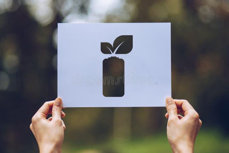 Sicherungsweltökologie-Konzept-Klimaerhaltung mit den Händen, die herausgeschnittenes Papier halten, lässt Batterieeinsparungs-En stockfotos