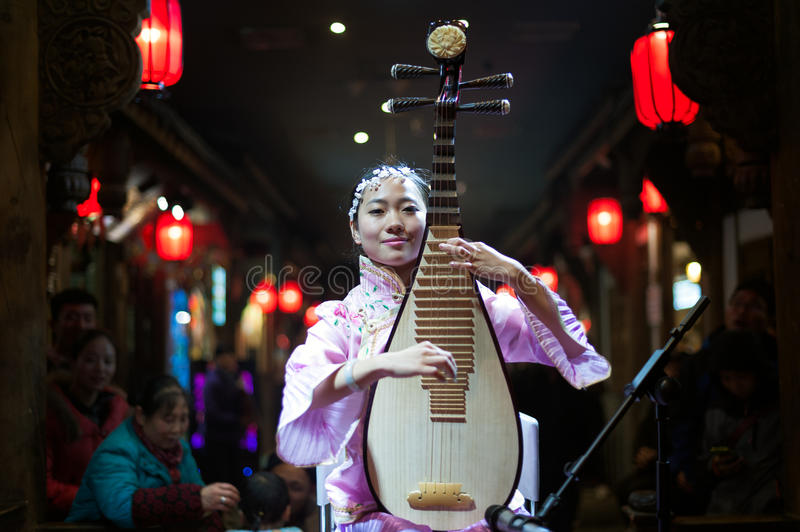 Sichuan Opera - Chengdu. Chengdu - December 29 2014: Chinese musician girl playing traditional chinese guitar or piba onstage at Chunxifang Chunxilu on December royalty free stock images