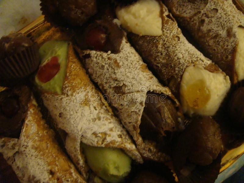 Sicilian Cannoli to the cream of pistachio, chocolate and cream on a tray. Italy royalty free stock image