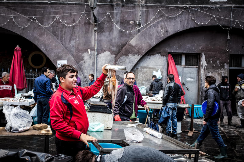 Sicilian fisherman shows an octopus in the fish market of Catania royalty free stock photo