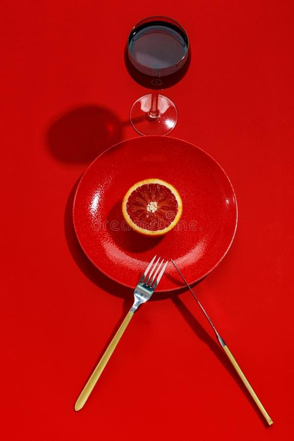 Sicilian orange snitt i halva p? en r?d platta Top besk?dar kopiera avst?nd id?rikt begrepp arkivbilder