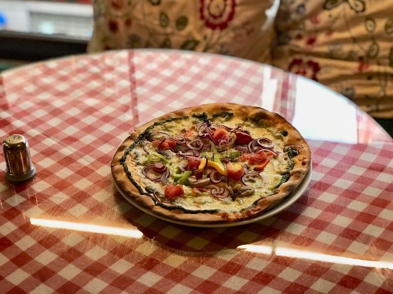 Sicilian pizza med lökcirklar, Pesto och vitlöksås tjänade som på röd bordduk arkivbilder