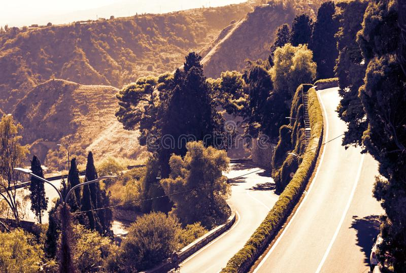 Sicily sunset with curvy serpentine road in green mountains - beautiful panorama of Taormina stock photography