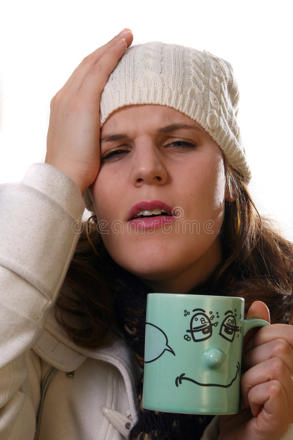 Sick. A young woman is holding a cup of tea. She is sick and in pain with winter gear on. Isolated over white with space for text stock photo