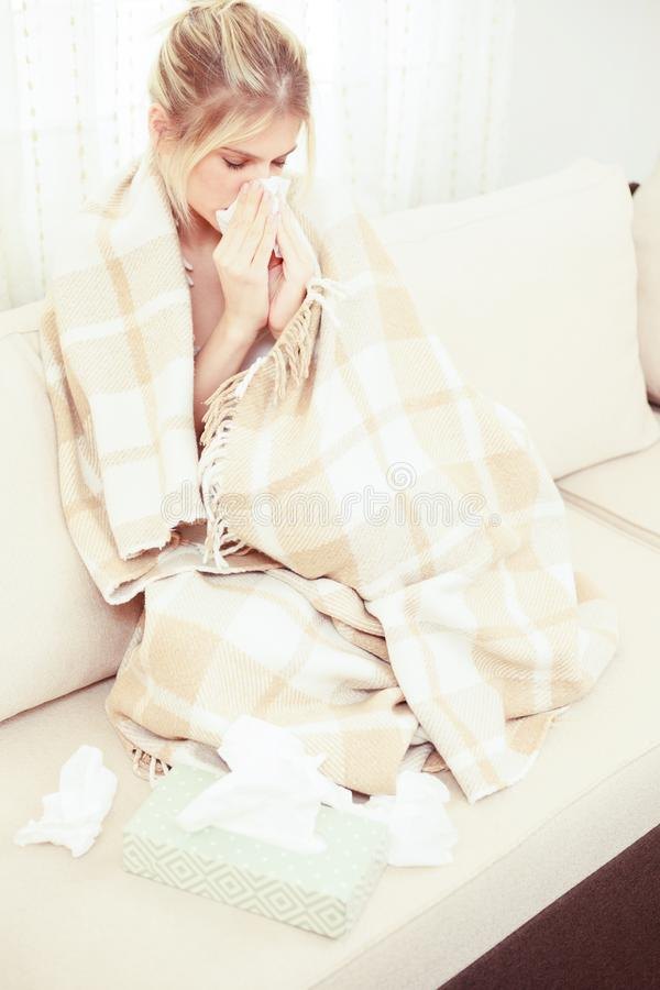Sick, allergic young woman sitting wrapped in a cozy blanket in living room, blowing her nose stock photo