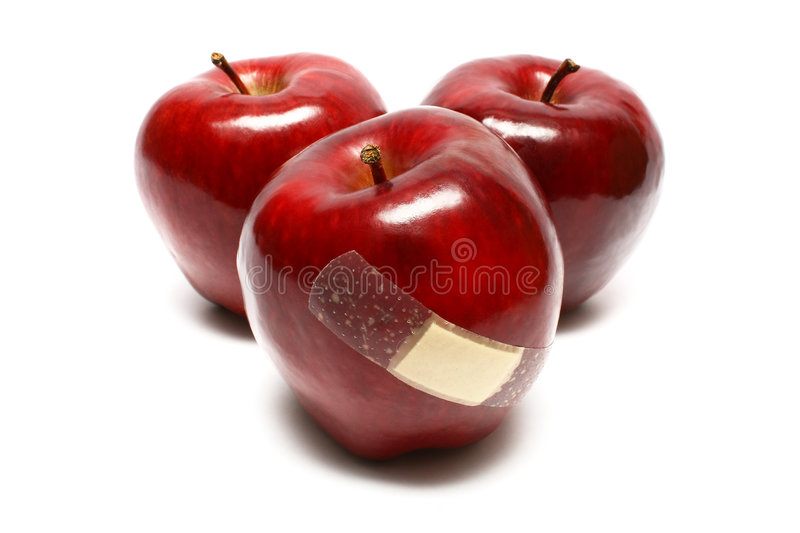 Sick Apples. Injured apples with plaster on white background royalty free stock images