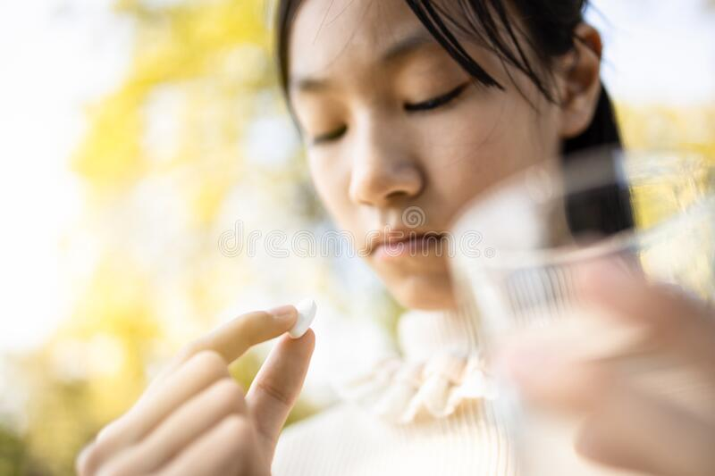 Sick asian child girl holding pill and glass of fresh water in hand,sad female teen taking medicine painkiller,antibiotic, stock image