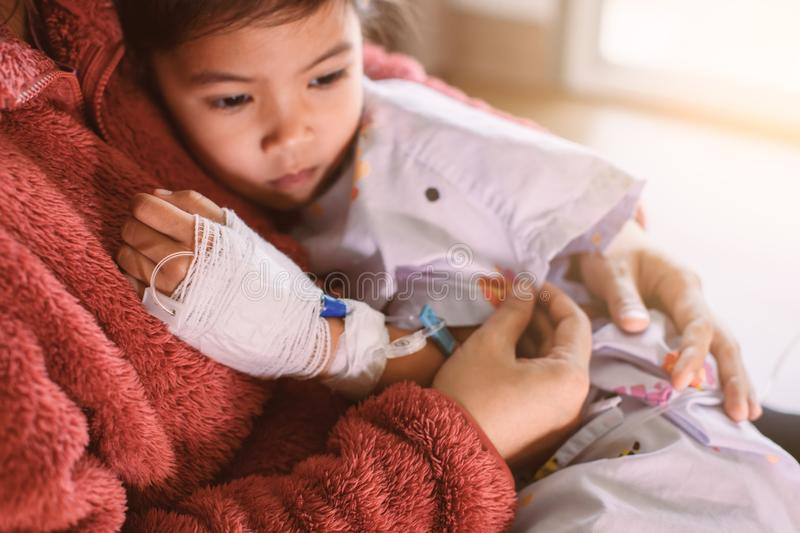 Sick asian child girl who have IV solution hugging her mother royalty free stock images