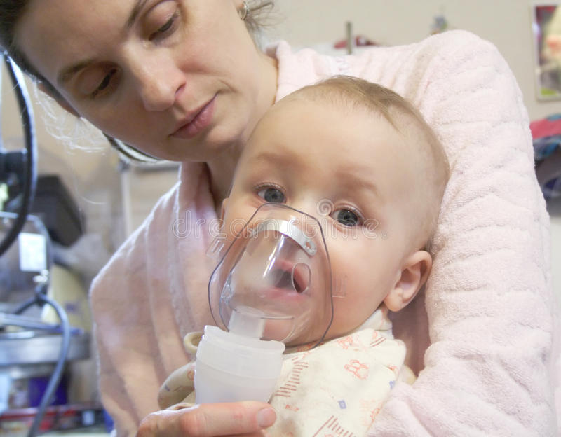 Sick baby with nebulizer mask. Mom and sick baby with nebulizer mask stock photo