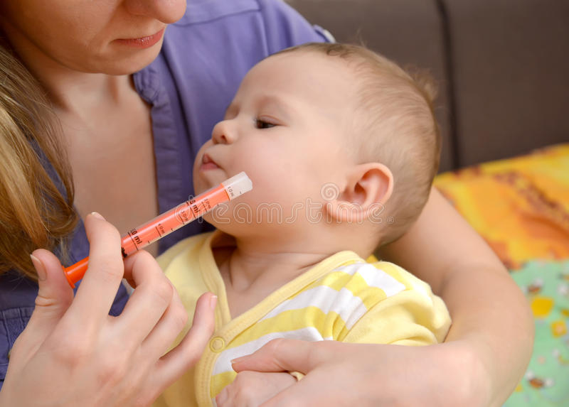 The sick baby refuses to take medicine by means of the batcher. Treatment stock photography