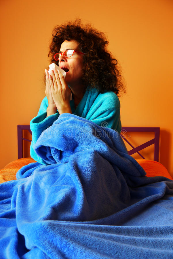 Mature Woman Sneezing in Bed. A mature woman of 49 sitting under a blue blanket in her bed, sneezing and coughing stock photography