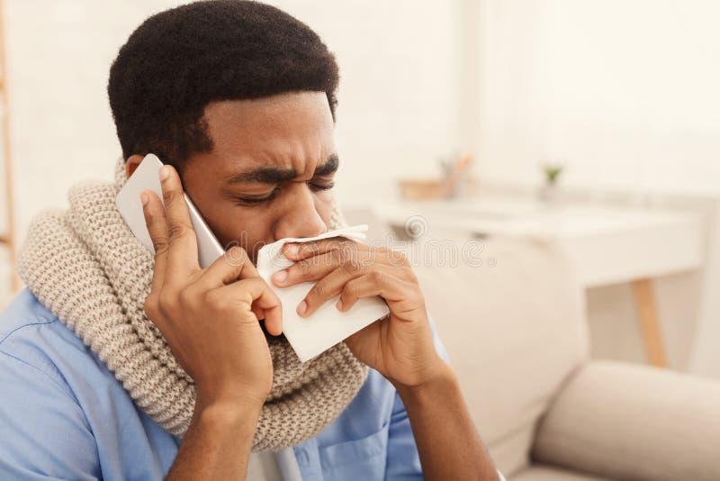 Sick black man calling on phone. to doctor stock photos