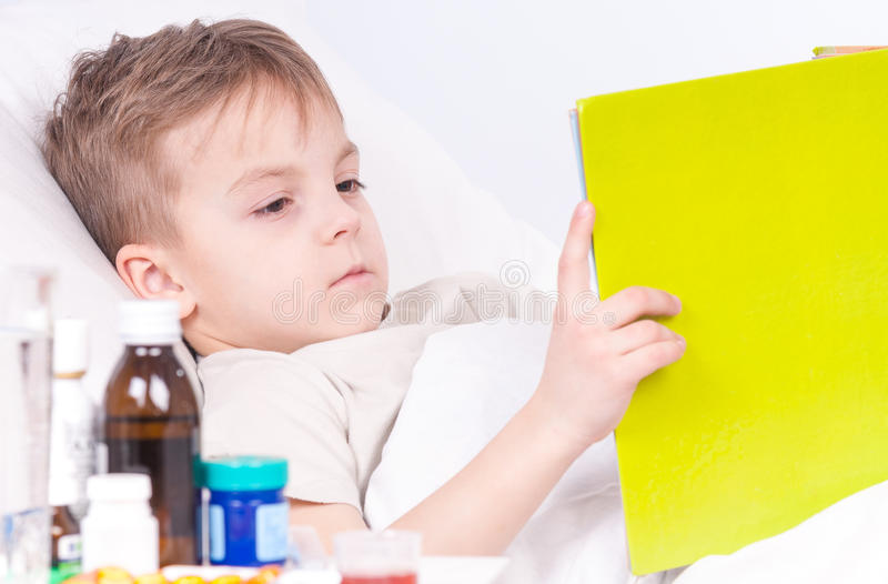 Sick boy in bed reading book royalty free stock photography