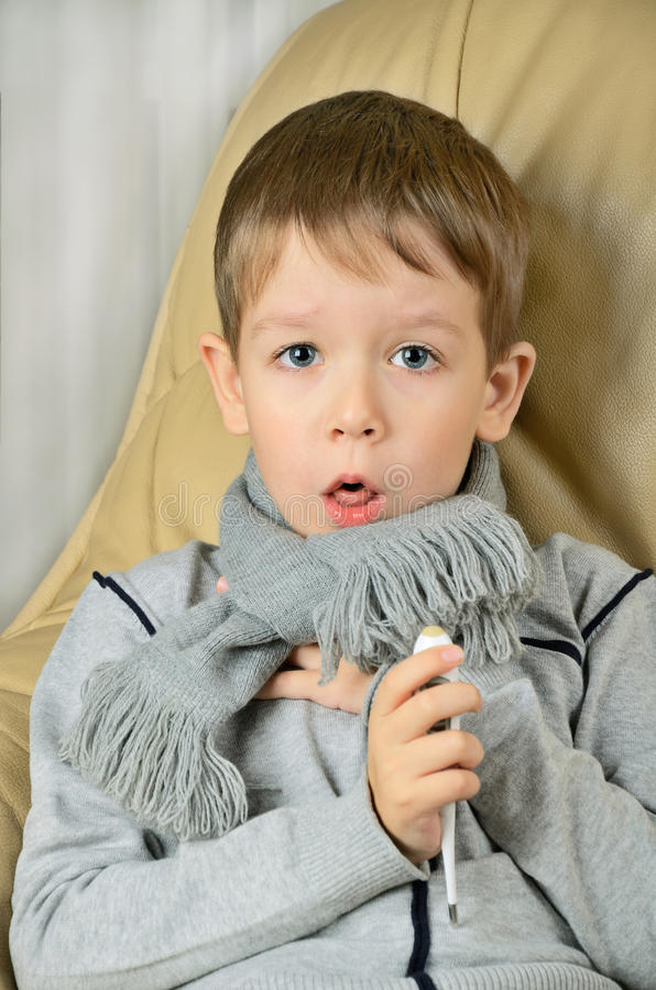 Sick boy coughing and holding a thermometer royalty free stock photography