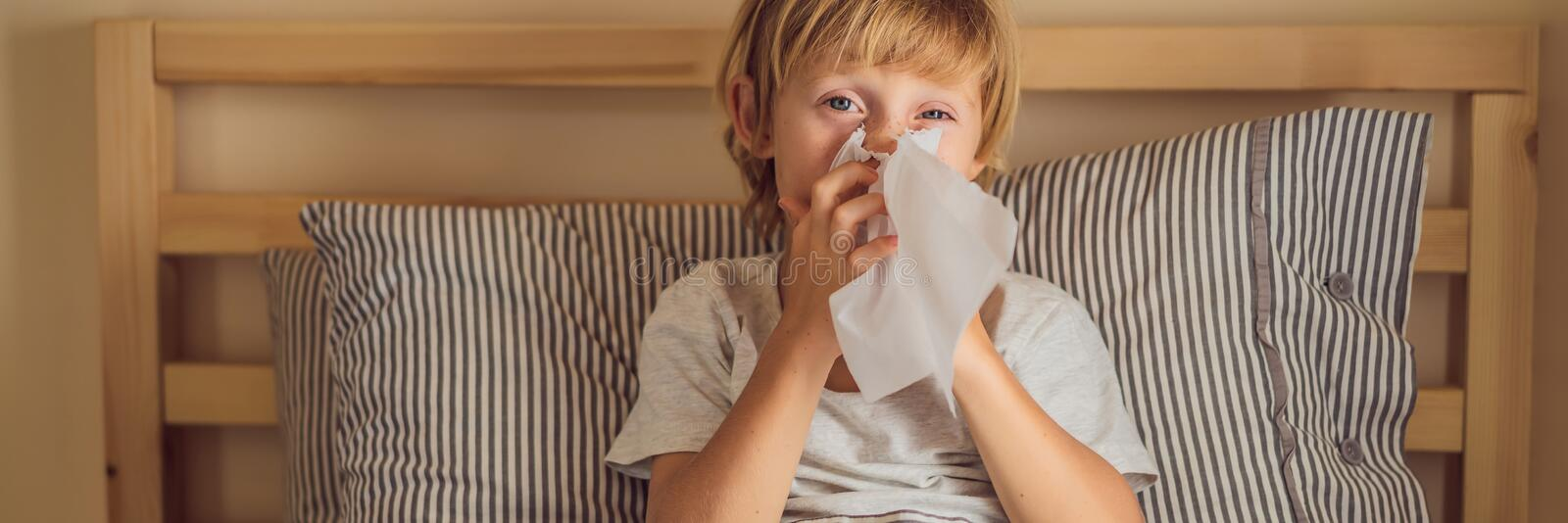 Sick boy coughs and wipes his nose with wipes. Sick child with fever and illness in bed BANNER, LONG FORMAT. Sick boy coughs and wipes his nose with wipes. Sick royalty free stock photo