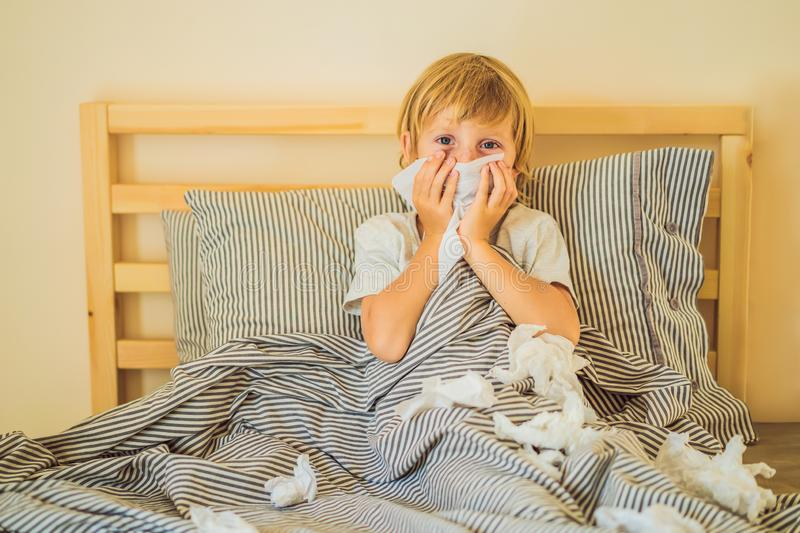 Sick boy coughs and wipes his nose with wipes. Sick child with fever and illness in bed royalty free stock photos