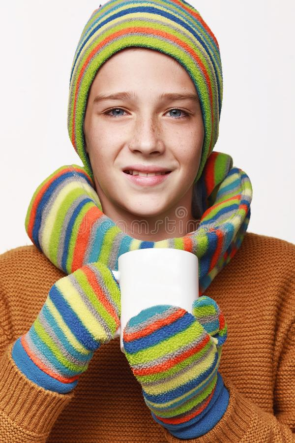 The sick boy holds a cup of tea, medicine, got sick. In a sweater, a cap, gloves, a disease, cold, flu, winter, fall. On a white background in studio stock image