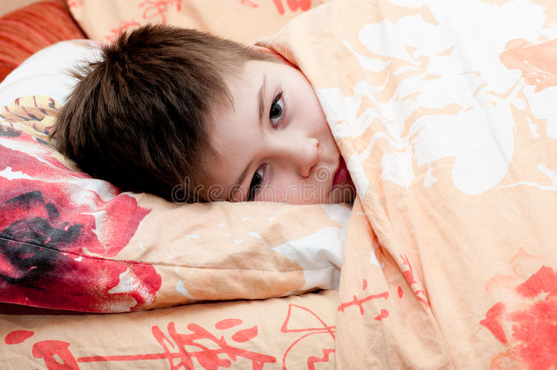 Download Sick boy lying in bed stock photo. Image of blanket, scarf - 27884700