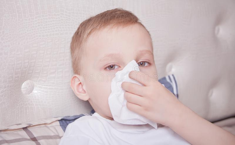 Sick boy lying in a bed and blowing her nose royalty free stock image