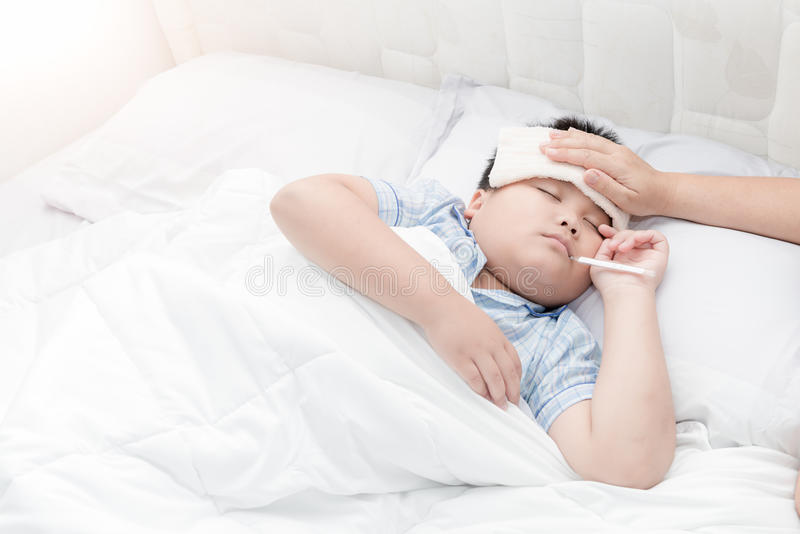 Sick boy with thermometer laying in bed and mother hand taking t royalty free stock image