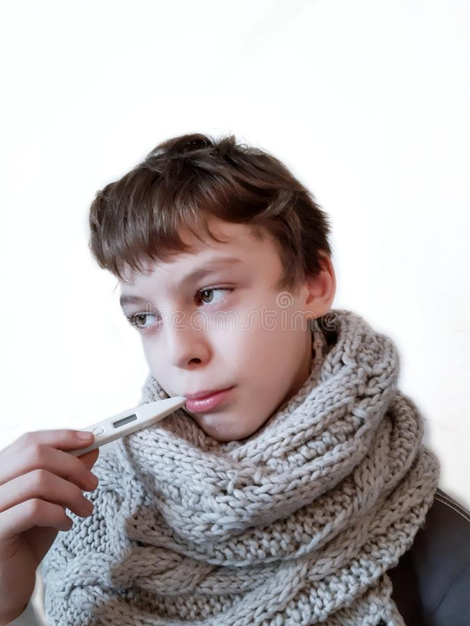 Sick boy with thermometer in mouth on white background royalty free stock photography