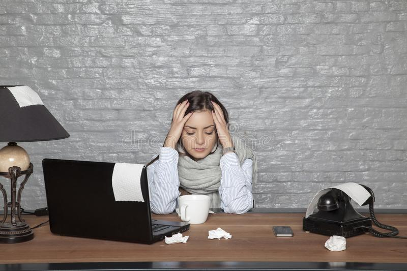 A sick business woman has a headache from a cold. Portrait of a business person stock image