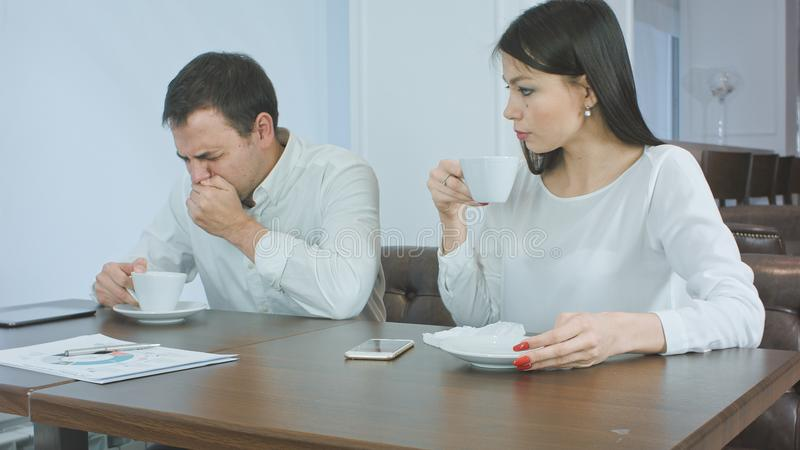 Sick businessman sneezing while anxious female checking his head for fever and giving him napkin royalty free stock photo
