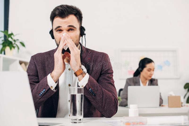 Sick call center operator with napkin blowing nose royalty free stock images