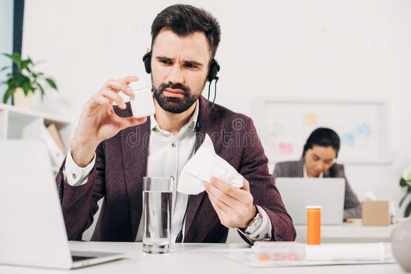 Sick call center operator sitting at desk and holding pill bottle and napkin stock image