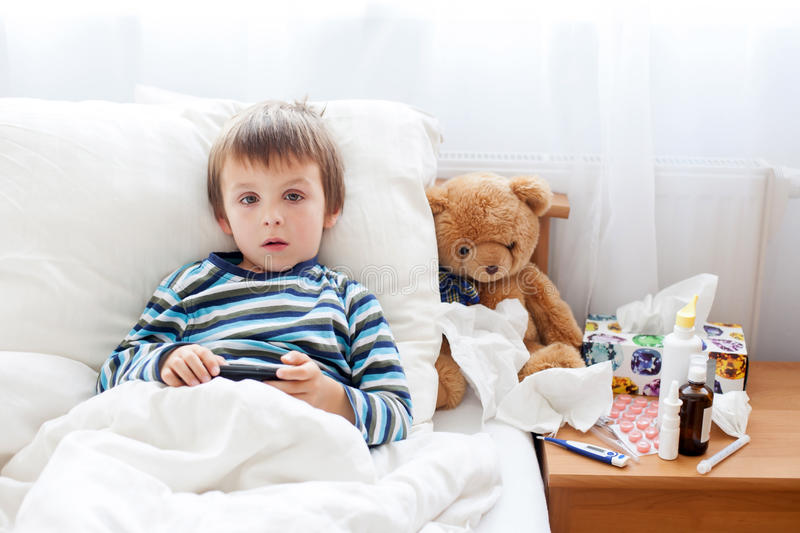 Sick child boy lying in bed with a fever, resting. At home stock photos