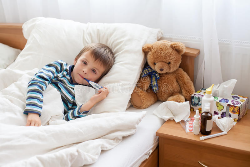 Sick child boy lying in bed with a fever, resting stock image