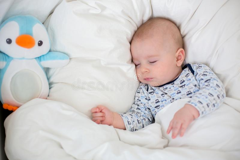 Sick child boy lying in bed with a fever, resting at home stock photo