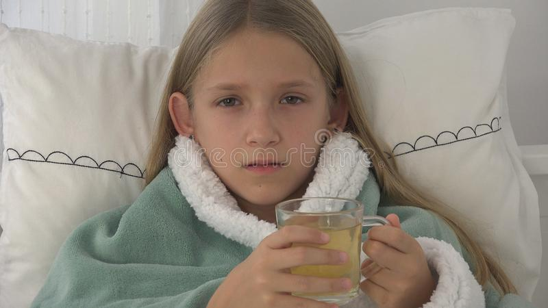 Sick Child Drinking Tea, Ill Kid in Bed, Suffering Girl, Patient in Hospital royalty free stock photos