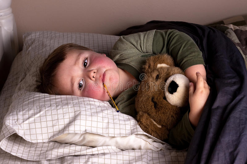 Sick child with fever stock photography