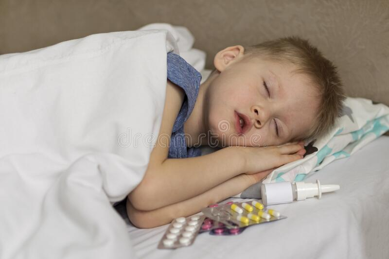 A sick child with a fever and a headache lies in bed. The child sleeps around drugs and pills. Flu colds disease virus. Bacterium stock photo