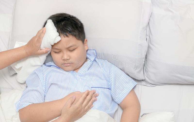 Sick child with fever and illness in bed, top view stock photography
