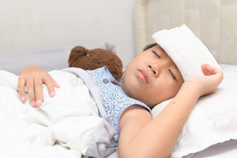 Sick child with high fever laying in bed royalty free stock images