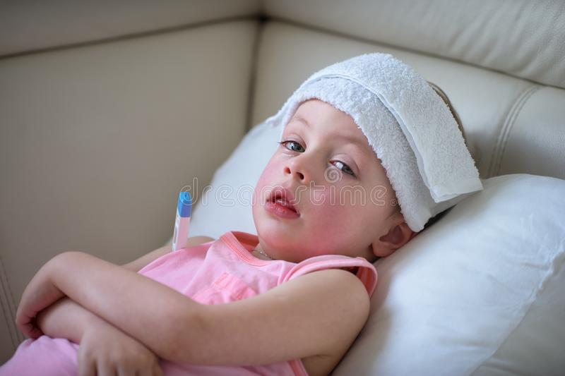 Sick child with high fever laying in bed stock images