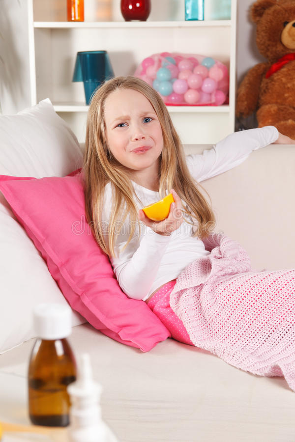 Sick child licking lemon royalty free stock images
