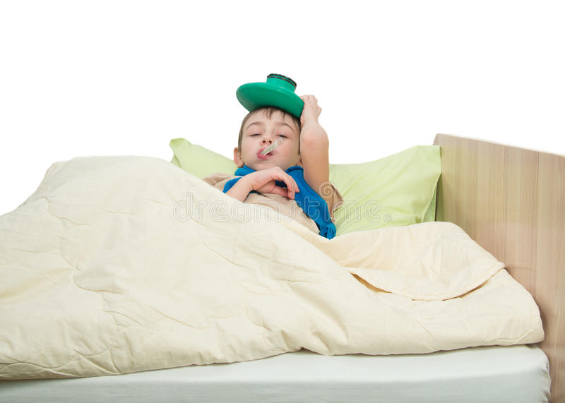Sick child lies in bed with a thermometer in his mouth and on his head holds an ice pack stock photos