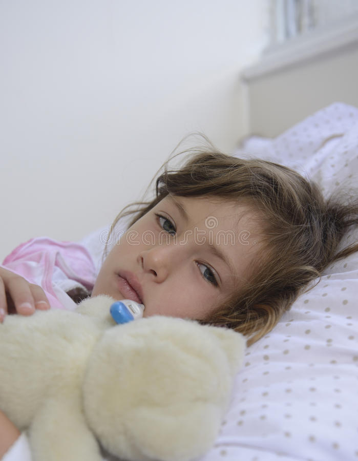 Sick child resting in bed royalty free stock image