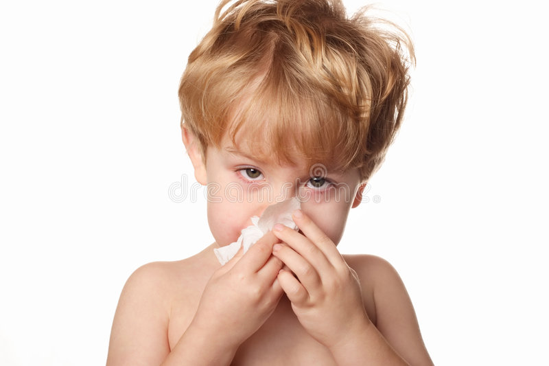 Sick Child wiping his nose. A sick young boy wiping his nose royalty free stock image