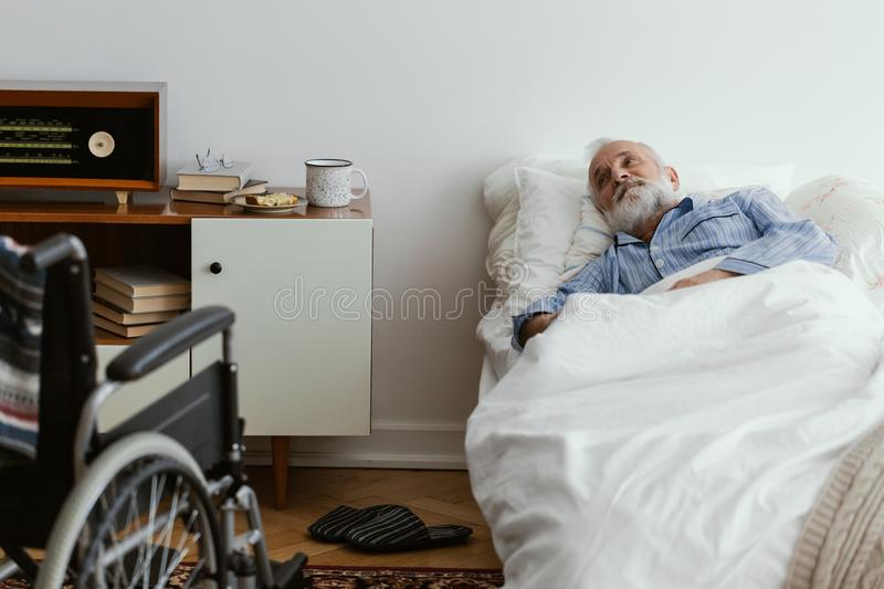 Sick elderly man wearing blue pajama lying in bed at nursing home. Sick elderly man wearing pajama lying in bed at nursing home royalty free stock photos